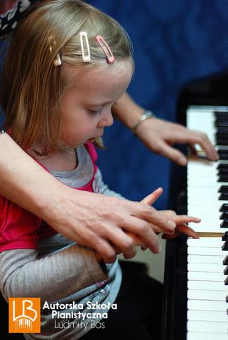 dziewczynka gra i przyciska klawisze pianina
